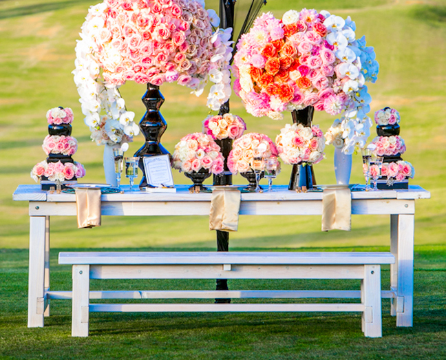 White picnic tables for rent with matching benches shown here with huge bright orchid displays. Photography by Brett Rose at The Crosby Club in Rancho Sante Fe, CA.