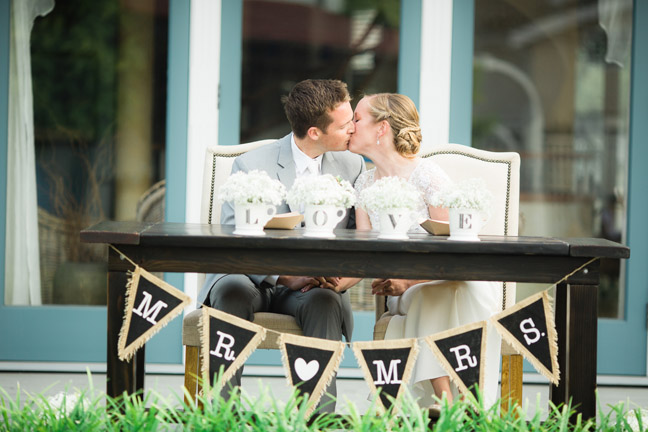 A wedding kiss in Coronado with farm table rentals for this bride and groom and their sweetheart table, high back Parson chairs, and burlap banner by Rustic Events. Photography by Garrett Richardson at Isabella Avenue, Coronado, CA.