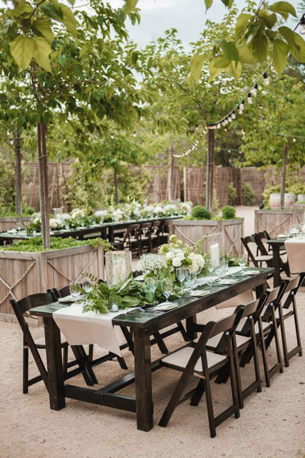 Wood table rentals with new fruitwood folding chairs by Rustic Events are surrounded by trees and market lights in the new Stone Meadow space at Temecula Creek Inn. Photography by Nichole Caldwell at Temecula Creek Inn in Wine-Country, Temecula, CA.