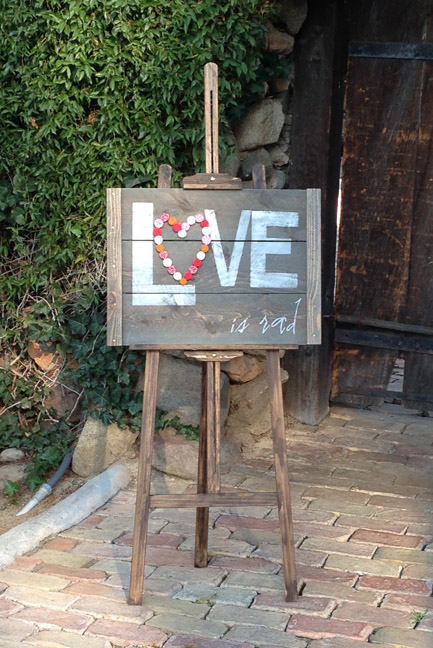 "Some of our signs :) ""Love is rad"" sign and easel for added rustic décor. Photography by Chris Wojdak at Rancho Vista Adobe, Vista, CA."