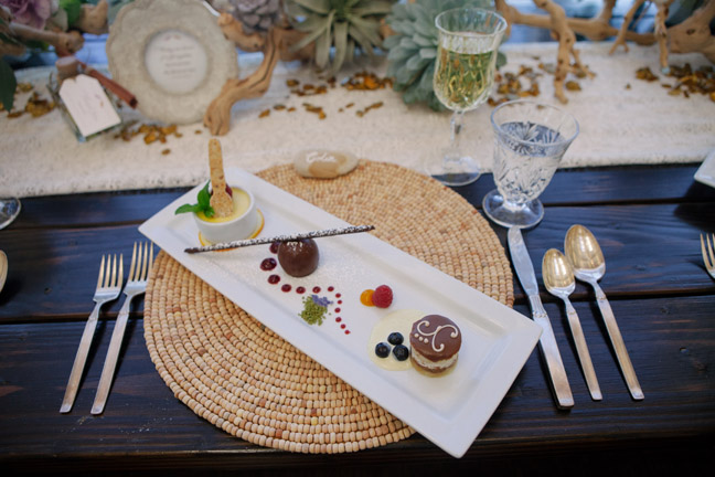 Fancy food displayed on wood rental tables from Rustic Events. Photography by Ashley Williams at The Marine Room in La Jolla, CA.