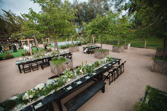 Espresso rustic table rentals with a mix of matching wood benches and fruitwood folding chairs. Photography by Nichole Caldwell taken at Temecula Creek Inn, Temecula , CA.